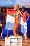 女性健身模型庆祝她的在阶段的胜利与旗子 免版税库存图片