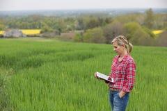 女性农夫与片剂一起使用 免版税库存照片