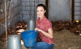 年轻女性农夫在农厂房子里 免版税库存图片
