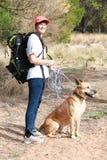 女性准备好与她的狗的灌木步行 免版税图库摄影