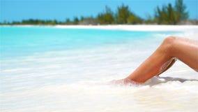 女性减肥在一个白色热带海滩的被晒黑的腿 缓慢的录影 影视素材