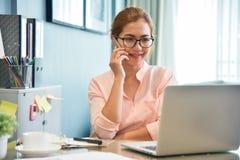 女性创造性的设计师谈话在手机在她的工作场所 免版税库存照片