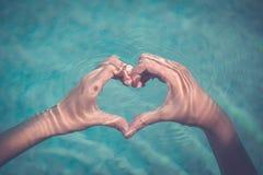 女性制造的心脏形状用手在水中 免版税库存照片