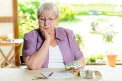 女性前辈计算她的预算 免版税库存图片