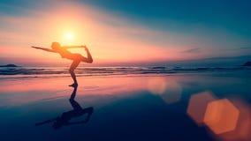 女性剪影执行在海滩的瑜伽锻炼 图库摄影