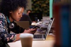 女性办公室工作者用在后运转的书桌的咖啡 免版税库存照片