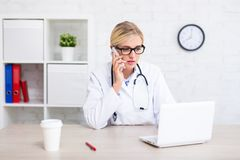 女性医生与计算机一起使用和谈话由电话在办公室 免版税库存照片
