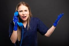 女性医生佩带洗刷叫喊在受话器 免版税库存图片