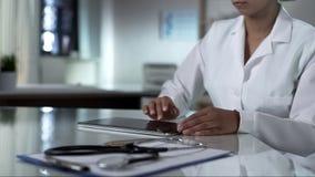 女性医生卷动片剂屏幕,检查患者测试结果,诊所 免版税库存图片