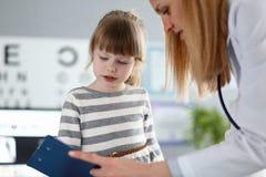 女性医生听的逗人喜爱的矮小的患者和写注册信息在剪贴板垫 免版税库存图片