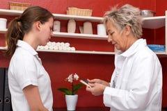 女性医生和学生在办公室 免版税库存照片