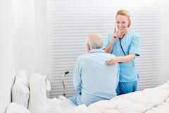 女性医生审查呼吸与一个病的前辈 库存照片