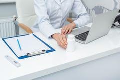 女性医生播种的射击有瓶子的药片 免版税图库摄影
