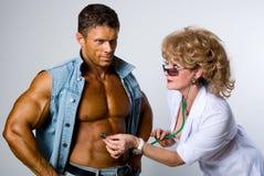 女性医生检查一名患者 免版税库存照片