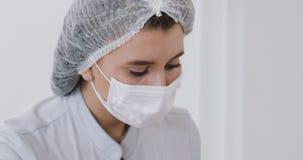 女性医生的面孔的特写镜头做射入做法的面具的 portrait医生 影视素材
