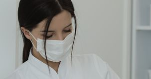 女性医生的面孔的特写镜头做射入做法的面具的 portrait?? 股票录像