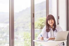 女性医生谈论与她的在窗口旁边的男性患者 免版税图库摄影