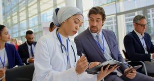 女性医生谈论在数字片剂在企业研讨会4k 股票录像