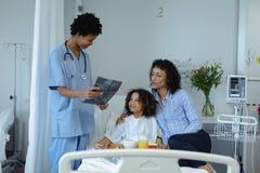 女性医生谈论在X-射线报告与母亲和儿子在病区 免版税库存图片