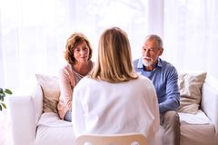 女性医生谈话与一对资深夫妇 免版税库存照片