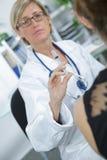 女性医生Injecting Drug对患者的With Syringe 图库摄影
