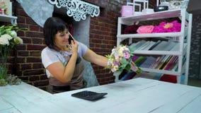 女性卖花人谈话在电话谈论花束的费用与顾客在花店 股票视频