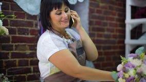 女性卖花人谈话在电话谈论花束的费用与顾客在花店 影视素材