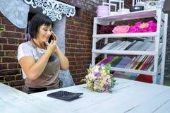 女性卖花人谈话在电话谈论花束的费用与顾客在花店 库存图片