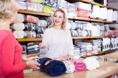年轻女性卖主为年迈的妇女提供床罩 图库摄影