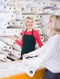 女性卖主55-60岁显示织品给年轻买家 免版税库存照片