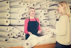 女性卖主显示织品给年轻买家 图库摄影