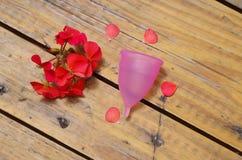 女性卫生学方面的产品-在旁边的月经杯子美丽的红色花,在木背景中 免版税库存图片
