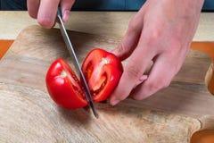女性厨师切与一把刀子的红色蕃茄在木切板 免版税图库摄影