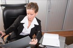 女性厨师在有很多文件的办公室 库存照片