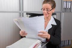 女性厨师在有很多纸的办公室 库存照片