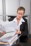 女性厨师在有很多纸的办公室 免版税库存照片