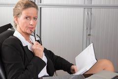 女性厨师在调查日历的办公室 免版税库存照片