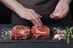 女性厨师调味料摩擦两在黑暗的背景的新鲜的未加工的ribeye牛肉 附近胡椒混合物,海盐 免版税库存图片