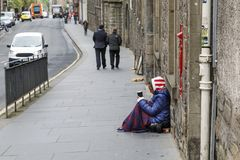 女性叫化子坐在一条拥挤的街上的路面 她拿着一个杯子 图库摄影