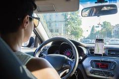 年轻女性司机使用触摸屏智能手机的和gps 免版税库存图片