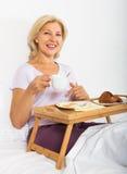 女性吃早餐在床 免版税图库摄影