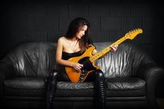 女性吉他弹奏者坐一个皮革长沙发 免版税库存照片