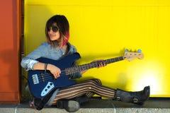 女性吉他弹奏者坐弹蓝色吉他的壁架 库存图片