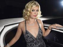 女性名人离开大型高级轿车 免版税库存图片
