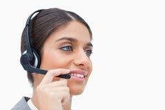 女性呼叫中心座席侧视图与耳机的 免版税库存照片