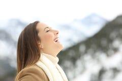 女性呼吸在山在冬天 库存照片