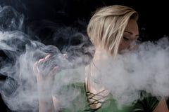 女性呼气烟和抽烟的蒸发器 免版税库存图片