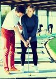 女性和男性高尔夫球运动员享受比赛 库存照片