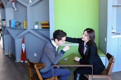 女性和男性年轻同事在加州聊天在午餐时间并且坐 免版税库存图片