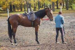 女性和驾驶马在跑马场在实践期间 库存图片